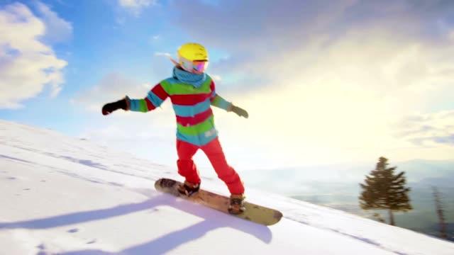 SLO MO femminile affettare sulla pista da sci snowboard