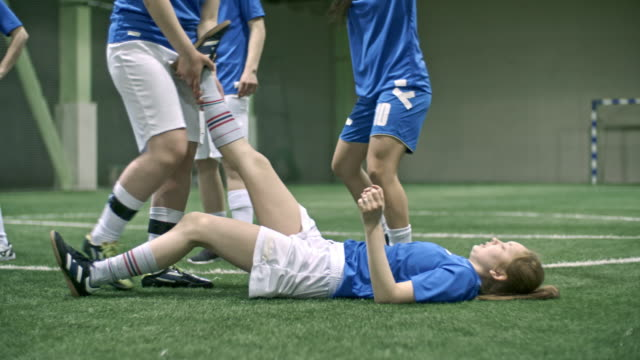 Female soccer player helping teammate relieve cramping