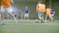 Female soccer player scoring goal during friendly match