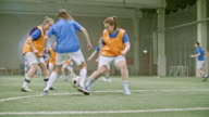 Female soccer player taking shot towards net and failing to score goal