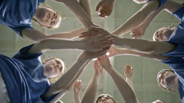Female soccer team stacking hands together
