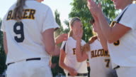 MS SLO MO Female softball teammates huddle before walking onto field during game