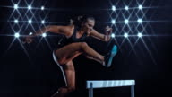 SLO MO DS Female sprinter in black outfit jumping over a hurdle at night
