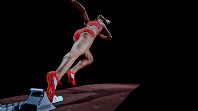 SLO MO Female sprinter in red outfit starting from the starting block
