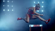 SLO MO DS Female sprinter jumping over a hurdle at night