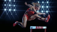 SLO MO DS Female sprinter leaping over a hurdle at night