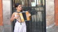 Female street musician plays accordion, MS