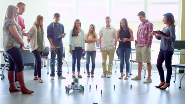 WS female student demonstrating robot to other students during robotics class in high school classroom