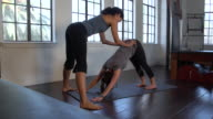 'MS PAN Female student practicing Yoga with instructor / Beverly Hills, California, United States'