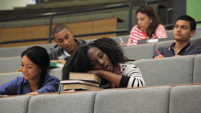 MS LA SELECTIVE FOCUS Female student sleeping amongst other students in lecture hall / London, England