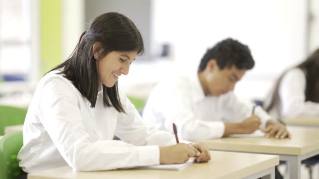 Female student smiling during an examination while answering the test
