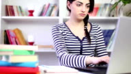 Female student studying at home with a laptop