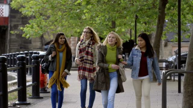 Weibliche Studenten, die zu Fuß über