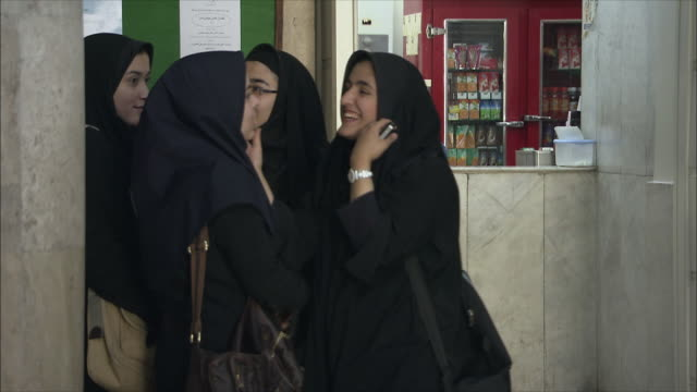 MS Female students wearing traditional clothing talking in University hall, Tehran, Iran