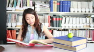 Female studing in library and reading book
