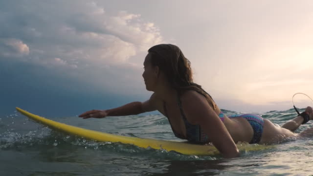 Female surfer paddling for wave in bikini on surfboard in the ocean at sunset in Southern France