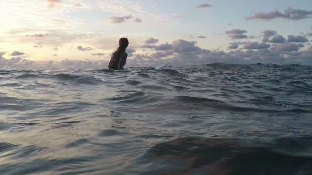 Female surfer paddling on surfboards in the ocean at sunset in Southern France