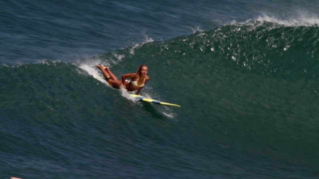 MS TS Female  Surfer riding wave and wipes out  / Haleiwa, Hawaii, United States