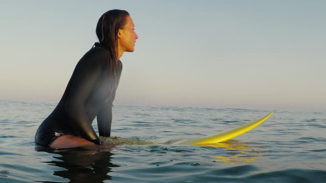Female surfer sitting on surfboard waiting for waves at deserted sandy beach at Atlantic ocean coast in the south of France.