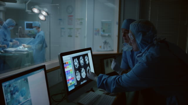Female surgeon and her assistant discussing head scans next to the operating room