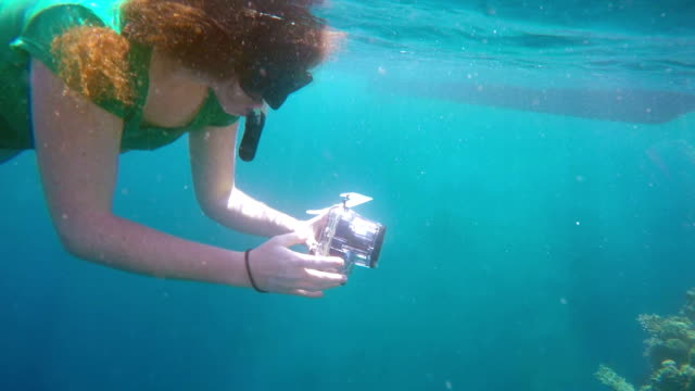 Female swimmer with underwater camera diving in North Bali coral reef