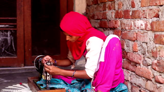 Female tailor, sewing clothes at home using sewing machine