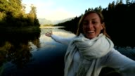Female takes self portrait at lake Matheson, NZ