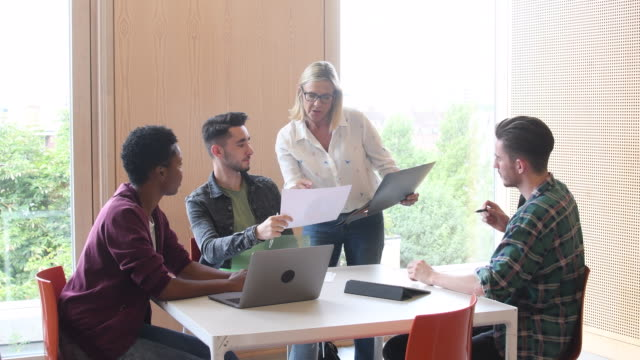 Female teacher advising students in meeting with laptop