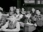 CLASSROOM DRAMATIZATION Female teacher at blackboard 'Carl Norcross' looking disinterested w/ hand to head shaking head when teacher calls on him...