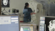 MS R/F Female technician assisting patient undergoing computed tomography seen through glass, computer monitors in foreground / Portland, Maine, USA