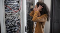 Female technician stressed about the cable mess in server rack
