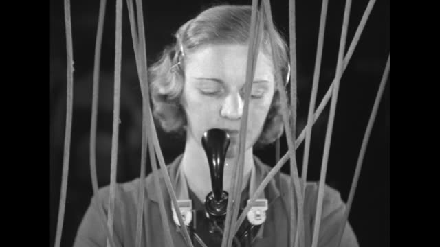 VS female telephone operator at switchboard her face seen though numerous cords speaking into chestmounted microphone /operator answers and completes...
