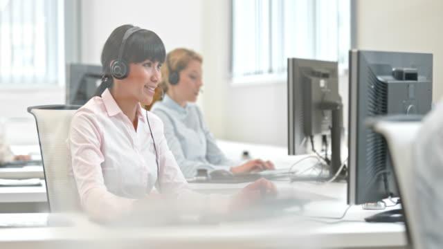 DS weibliche Telefonist sprechen auf ihrem Schreibtisch