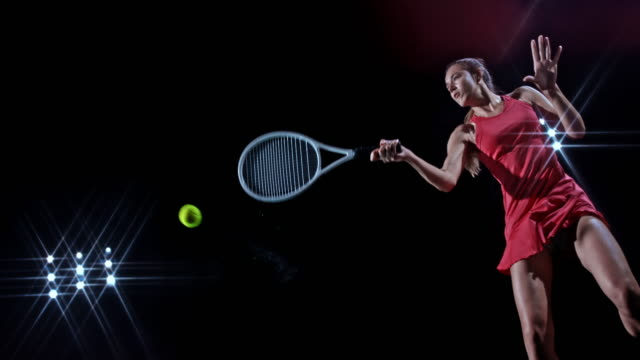 SLO MO Female tennis player hitting the ball with a backhand on black background
