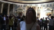 A female tourist admires the ceiling of The Pantheon, Rome