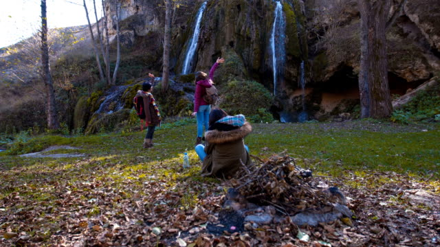Female tourist take photos of her friends near waterfall