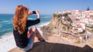 Female tourist taking pictures of village on cliffs by ocean