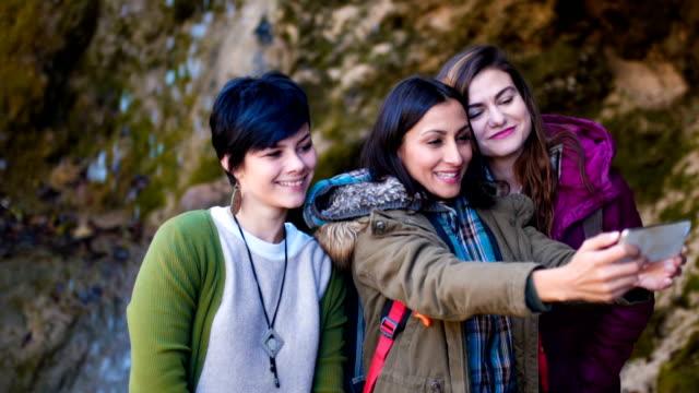 Female tourists taking a selfie near waterfall