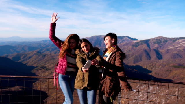 Female tourists taking selfie on the top of mountain