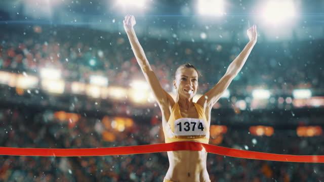 Female track and field runner crosses finishing line