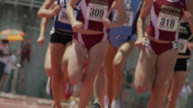 SLO MO LA MS CU Female track athletes running around track during race / Atlanta, Georgia, USA