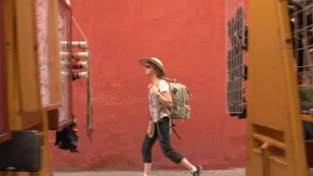 Female traveler walks past street vendors in Queretaro