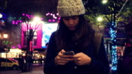 Female using smart phone in city at night