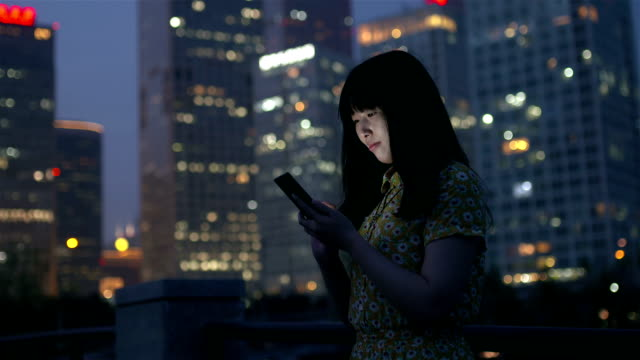 Female using smartphone in city at night
