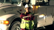 Female utility worker standing by truck