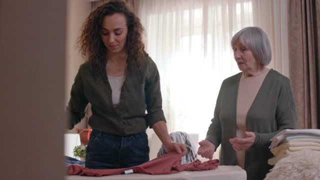 Female volunteer ironing clothes for senior lady