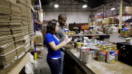 Female volunteer walking into focus while sorting donated food in charity warehouse