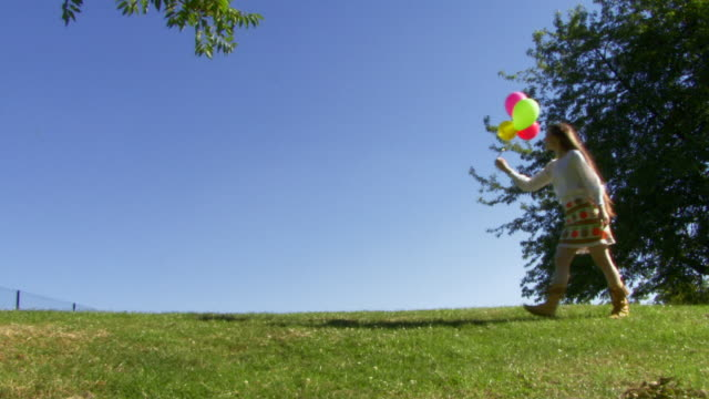 Female walking with balloons and releasing them