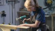 Female woodworker grinding a piece of wood