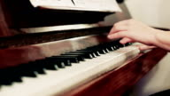 Female's hand playing a piano